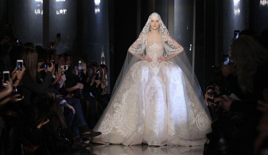 Le défilé Haute-Couture Printemps-Eté 2013 du Libanais Elie Saab s'est déroulé mercredi matin à Paris. Comme à son habitude, le créateur a présenté une collection légère et aérienne, faite de dentelle, de pierreries et de broderies fines. Qu'elles soient nacrées ou fleuries, les robes –cintrées à la taille- ont été parfaitement portées par des mannequins à peine maquillées, laissant le regard libre de ne se porter que sur leurs élégantes tenues.
