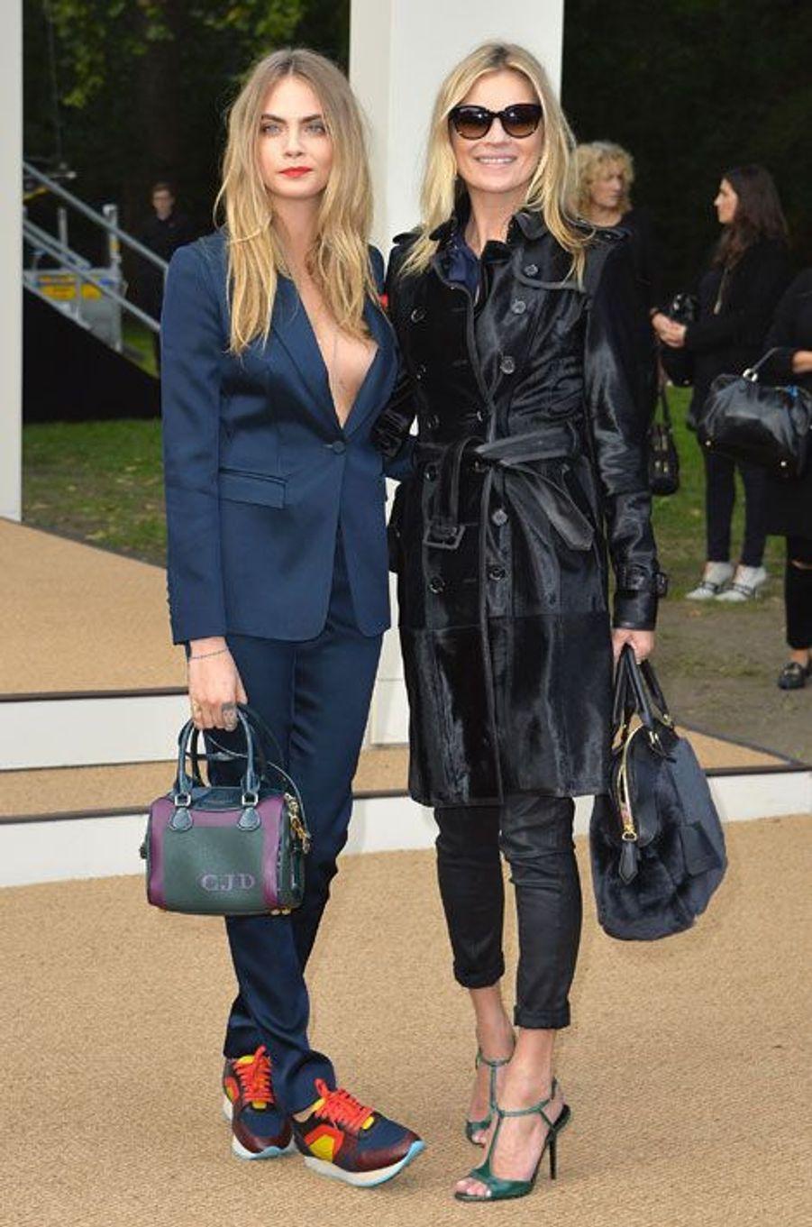 Les mannequins Cara Delevingne et Kate Moss assistent au défilé printemps-été 2015 Burberry Prorsum dans des tenues de la griffe, lors de la Gas...