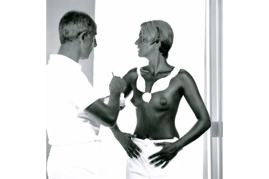 """Le couturier définissait ainsi sa collection d'hiver 1969-1970: """"J'ai voulu suivre le corps tel qu'il est"""". Fidèle à son idée de libérer la femme, il a dessiné ses modèles à même la peau : sur le buste de Tania, le couturier esquisse au pinceau et à la peinture blanche le col d'un vêtement."""