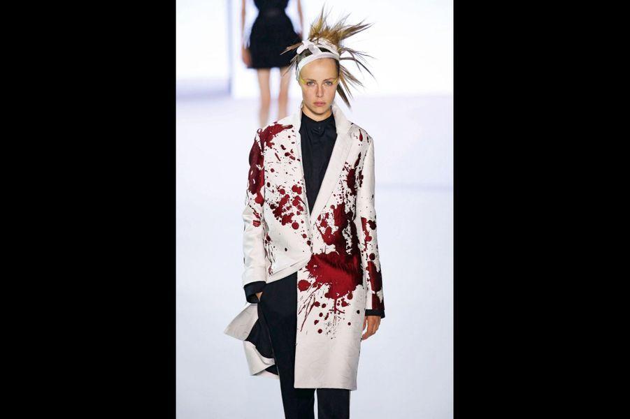 Haider Ackermann : Coupe iroquoise, pantalon skinny et manteau en satin éclaboussé de taches rouges tissées : la femme Ackermann est une guerrière poétique.