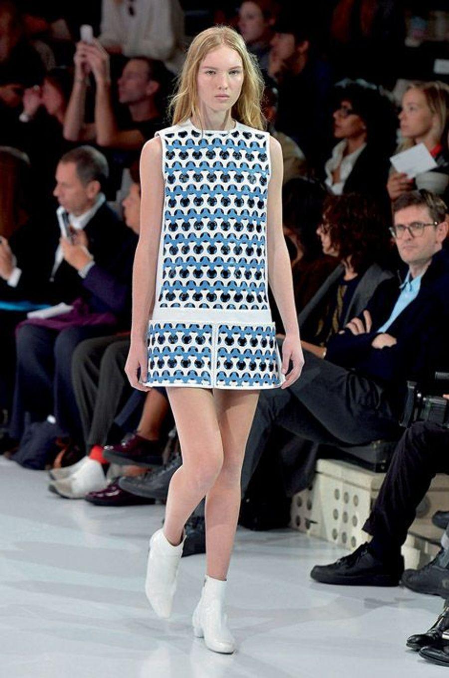 Futurisme des années 1960 et imprimés géométriques pour le retour de la maison sur les podiums après treize ans d'absence. Dans la cour Carrée du Louvre, le final du défilé Dior. En tête, le mannequin porte un pull court festonné en jacquard de laine bleu cobalt sur une robe chemise en voile de coton.Un champ de 400 000 delphiniums et une forêt de Smartphone. Si le réseau est saturé autour des podiums, c'est que les créateurs conviés à la Fashion Week ne manquent pas d'inspiration. Avec une collection « singulièrement futuriste et étrangement romantique », Raf Simons a donné le ton pour cette semaine de shows spectaculaires relayés dans le monde entier sur les réseaux sociaux. En plein mois d'octobre, la capitale française a décliné le printemps prochain en 91 défilés et une promesse : le pouvoir de séduction revient en force avec une mode ultra féminine. Alors que la femme fleur de Dior dégage pureté et simplicité, la dame de fer choisit le clinquant : pendant huit jours, la tour Eiffel a affiché « La mode aime Paris ».Justicière de l'espace aux cheveux roses tout droit sortie de studios d'animation japonais, tribu de nomades aux crêtes iroquoises acidulées, gladiatrices aux cuissardes en vinyle… Quand la mode rencontre la technologie et l'univers numérique, les enseignes de prêt-à-porter mêlent l'esthétique des jeux vidéo ou des dessins animés aux codes vestimentaires de la rue. Avant-garde et influences rebelles venues du punk ou du rock. Un cocktail détonant pour figurer des héroïnes modernes.Echappée belle porte « N° 5 »… Quand Karl Lagerfeld prend les commandes de la « Chanel Airlines », le Grand Palais devient l'aéroport « Paris Cambon », temple de l'escale aérienne. Entre les comptoirs d'enregistrement et les bancs métalliques, circulent des vacancières sophistiquées mais décontractées, casquettes à l'envers ou chemises nouées autour de la taille. « J'aime cette idée de vêtements faits de matières très riches, et portés comme du streetwear », dit le couturie