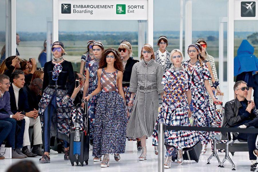 Dans la cour Carrée du Louvre, le final du défilé Dior. En tête, le mannequin porte un pull court festonné en jacquard de laine bleu cobalt sur une robe chemise en voile de coton.Un champ de 400 000 delphiniums et une forêt de Smartphone. Si le réseau est saturé autour des podiums, c'est que les créateurs conviés à la Fashion Week ne manquent pas d'inspiration. Avec une collection « singulièrement futuriste et étrangement romantique », Raf Simons a donné le ton pour cette semaine de shows spectaculaires relayés dans le monde entier sur les réseaux sociaux. En plein mois d'octobre, la capitale française a décliné le printemps prochain en 91 défilés et une promesse : le pouvoir de séduction revient en force avec une mode ultra féminine. Alors que la femme fleur de Dior dégage pureté et simplicité, la dame de fer choisit le clinquant : pendant huit jours, la tour Eiffel a affiché « La mode aime Paris ».Justicière de l'espace aux cheveux roses tout droit sortie de studios d'animation japonais, tribu de nomades aux crêtes iroquoises acidulées, gladiatrices aux cuissardes en vinyle… Quand la mode rencontre la technologie et l'univers numérique, les enseignes de prêt-à-porter mêlent l'esthétique des jeux vidéo ou des dessins animés aux codes vestimentaires de la rue. Avant-garde et influences rebelles venues du punk ou du rock. Un cocktail détonant pour figurer des héroïnes modernes.Echappée belle porte « N° 5 »… Quand Karl Lagerfeld prend les commandes de la « Chanel Airlines », le Grand Palais devient l'aéroport « Paris Cambon », temple de l'escale aérienne. Entre les comptoirs d'enregistrement et les bancs métalliques, circulent des vacancières sophistiquées mais décontractées, casquettes à l'envers ou chemises nouées autour de la taille. « J'aime cette idée de vêtements faits de matières très riches, et portés comme du streetwear », dit le couturier. Les passagères du terminal « 2C » sont les ambassadrices d'une exigence bleu, blanc, rouge. L'élégance et le confort d'u