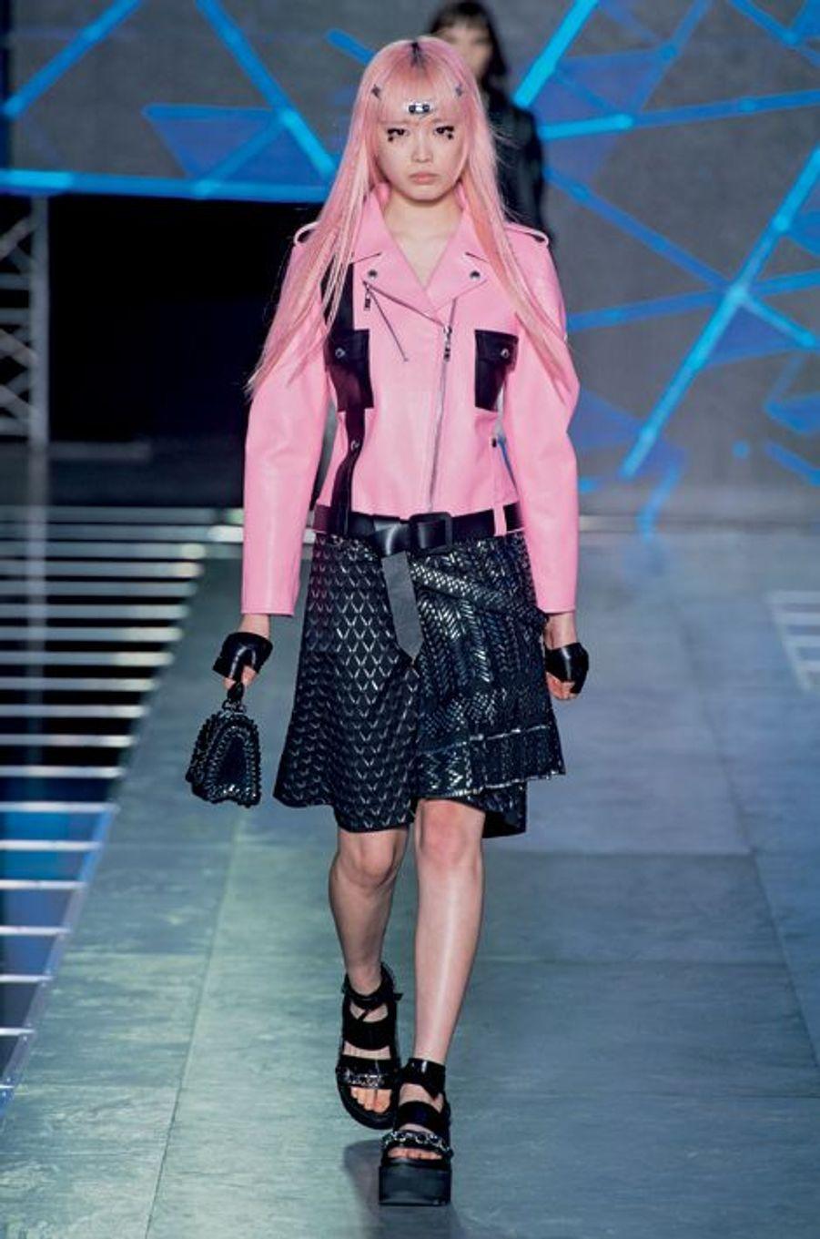 Ode à la culture geek : perfecto et jupe en soie avec des pièces thermocollées.Dans la cour Carrée du Louvre, le final du défilé Dior. En tête, le mannequin porte un pull court festonné en jacquard de laine bleu cobalt sur une robe chemise en voile de coton.Un champ de 400 000 delphiniums et une forêt de Smartphone. Si le réseau est saturé autour des podiums, c'est que les créateurs conviés à la Fashion Week ne manquent pas d'inspiration. Avec une collection « singulièrement futuriste et étrangement romantique », Raf Simons a donné le ton pour cette semaine de shows spectaculaires relayés dans le monde entier sur les réseaux sociaux. En plein mois d'octobre, la capitale française a décliné le printemps prochain en 91 défilés et une promesse : le pouvoir de séduction revient en force avec une mode ultra féminine. Alors que la femme fleur de Dior dégage pureté et simplicité, la dame de fer choisit le clinquant : pendant huit jours, la tour Eiffel a affiché « La mode aime Paris ».Justicière de l'espace aux cheveux roses tout droit sortie de studios d'animation japonais, tribu de nomades aux crêtes iroquoises acidulées, gladiatrices aux cuissardes en vinyle… Quand la mode rencontre la technologie et l'univers numérique, les enseignes de prêt-à-porter mêlent l'esthétique des jeux vidéo ou des dessins animés aux codes vestimentaires de la rue. Avant-garde et influences rebelles venues du punk ou du rock. Un cocktail détonant pour figurer des héroïnes modernes.Echappée belle porte « N° 5 »… Quand Karl Lagerfeld prend les commandes de la « Chanel Airlines », le Grand Palais devient l'aéroport « Paris Cambon », temple de l'escale aérienne. Entre les comptoirs d'enregistrement et les bancs métalliques, circulent des vacancières sophistiquées mais décontractées, casquettes à l'envers ou chemises nouées autour de la taille. « J'aime cette idée de vêtements faits de matières très riches, et portés comme du streetwear », dit le couturier. Les passagères du terminal « 2C » sont le