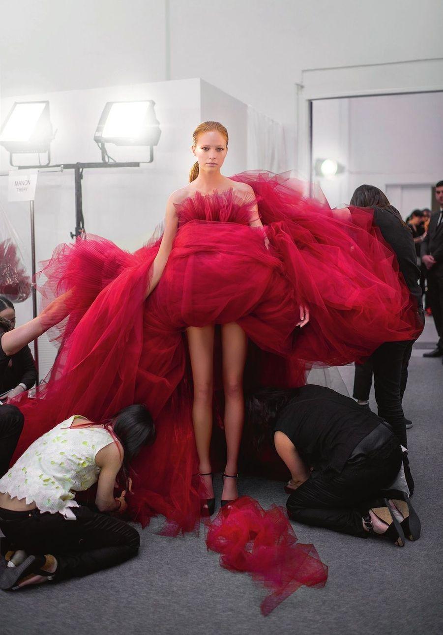 Backstage, c'est l'effervescence. Pas seulement à cause des métrages de tulle qui enrubannent le corps des mannequins comme cette robe Tamaris. Les filles s'interpellent, les couturières retouchent à la dernière minute. Mais, sur le podium, ce sont des pièces travaillées comme des bijoux baroques qui défilent avec majesté.