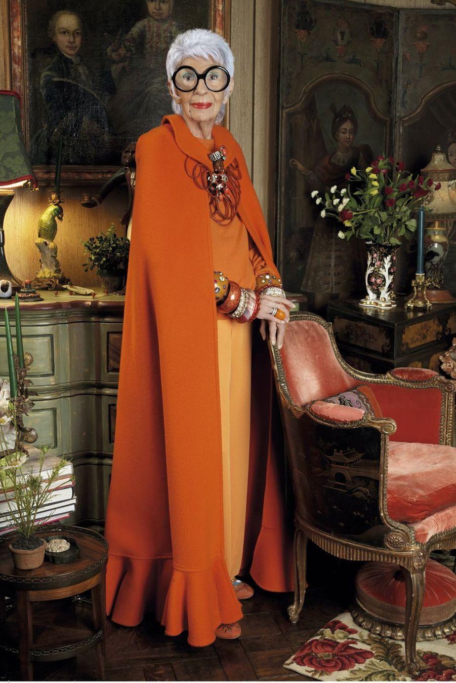 Iris, photographiée chez elle : décor Grand Siècle, petites lampes, bibelots et fringues partout.