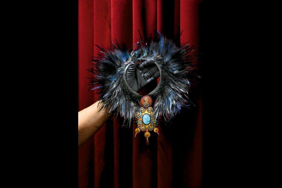 Collier en or ciselé et titane et en plumes de coq, de héron cendré, de faisan, d'autruche, orné d'un médaillon en jaspe rouge, d'un camée en turquoise, décorés d'apatites et de grenats.