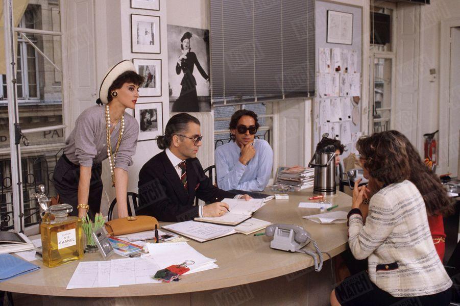 Karl Lagerfeld avec Inès de la Fressange dans les ateliers de la maison Chanel, avec qui elle vient de signer un contrat d'exclusivité de 7 ans,en juillet 1984.
