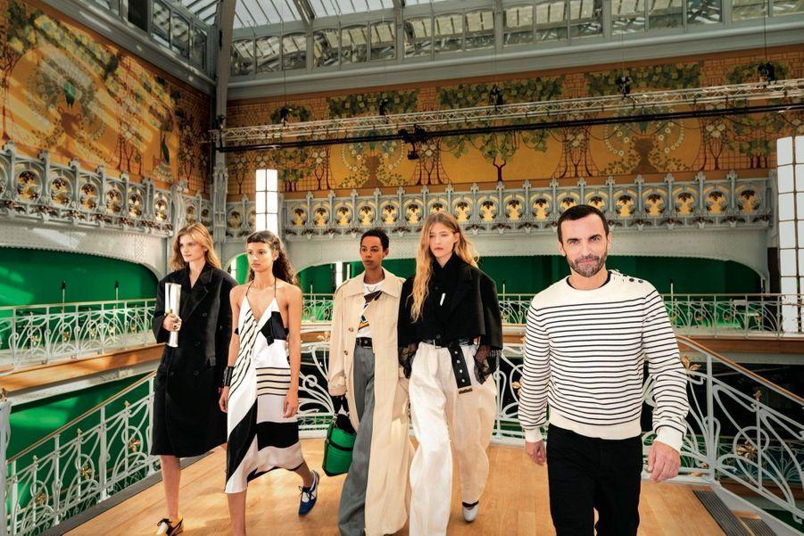 Louis Vuitton Nicolas Ghesquière et ses modèles, dans un monument de la mode qui fête ses 150 ans. Fresques jaune d'or et écrans verts pour incrustations vidéo.