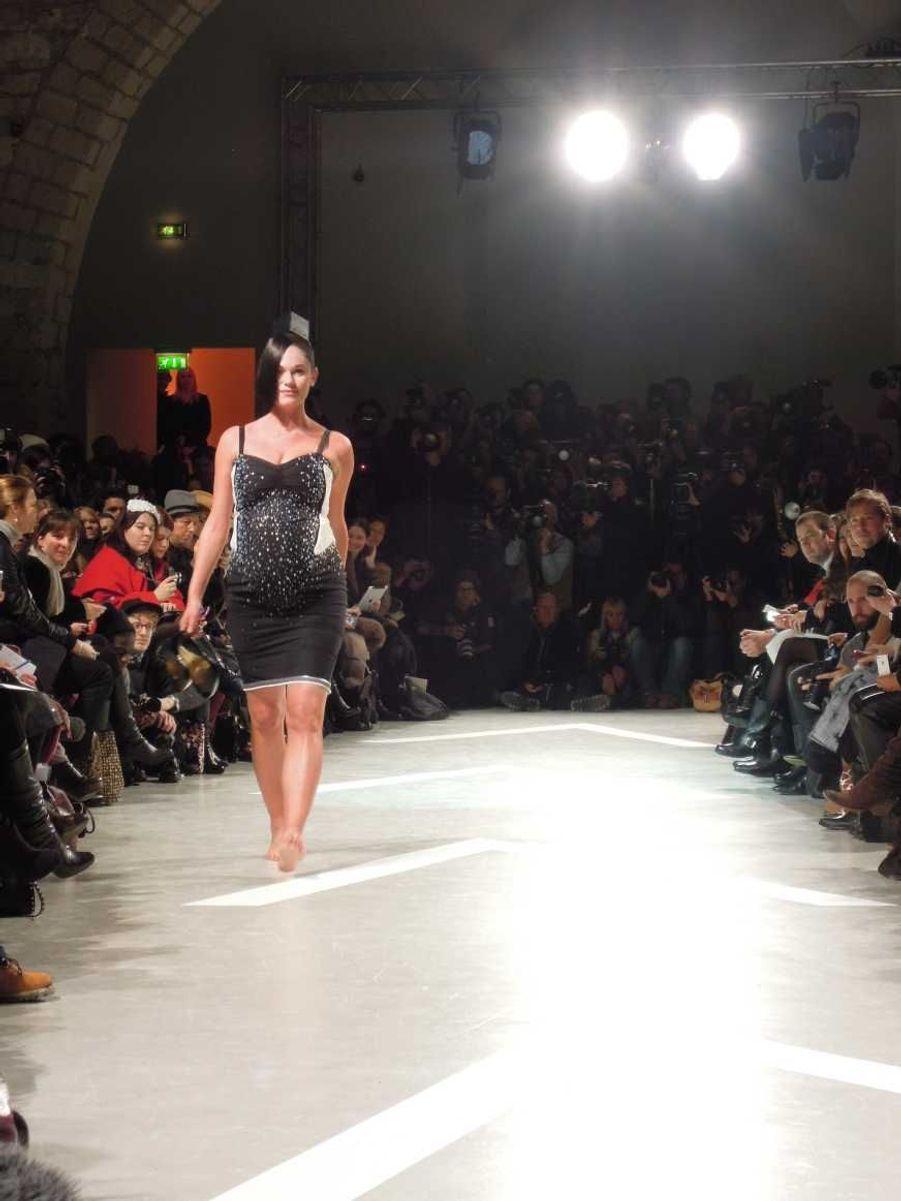 Un modèle est apparu avec un ventre plus qu'arrondi, ses chaussures à talon à la main et un sourire réjoui.