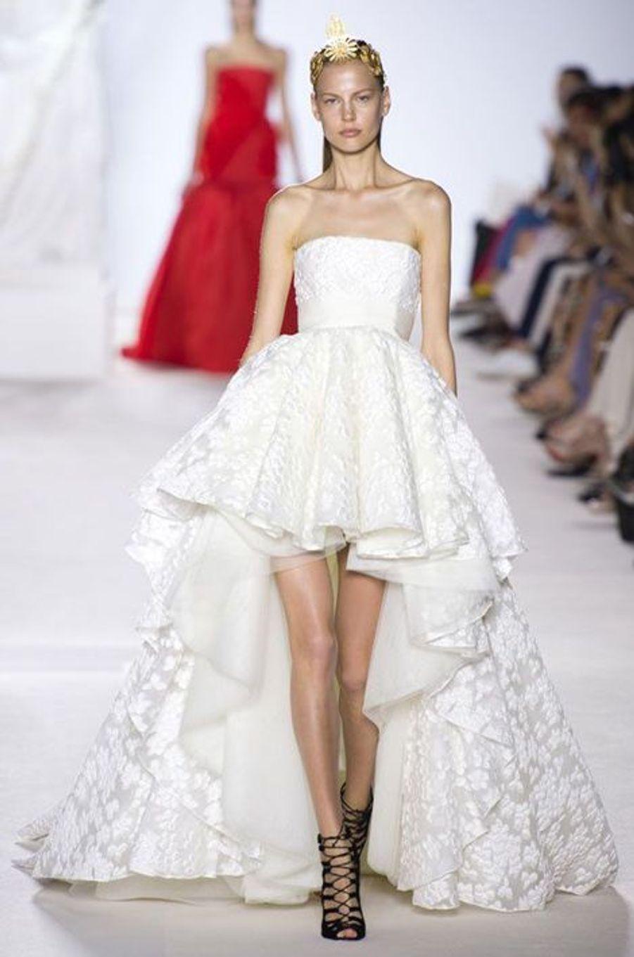 Issue de la collection haute- couture automne- hiver 2013- 2014, cette robe asymétrique rompt avec la traditionnelle robe de mariée. Une large ceinture blanc cassé marque la taille.