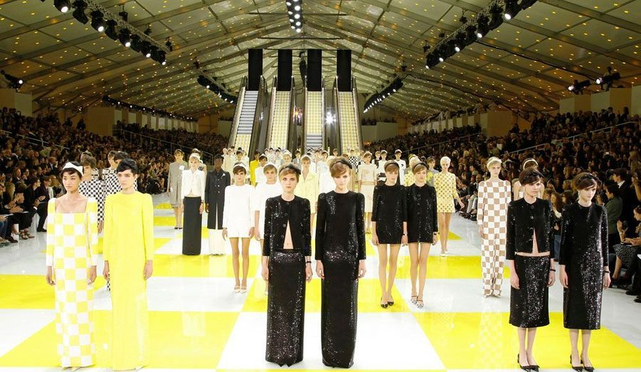En ce dernier jour de la Fashion Week parisienne, Marc Jacobs a présenté la collection prêt-à-porter printemps-été 2013 de Louis Vuitton. Le créateur américain a une nouvelle fois fait dans l'originalité en installant des escalators géants sur un sol en dallages rappelant le célèbre motif du maroquinier. Sous une immense tente dressée dans la Cour carrée du Louvre, les mannequins ont descendu deux par deux les escaliers mécaniques avec de petites robes droites à carreaux, d'inspiration très 60's et des tailleurs minimalistes. Côté couleurs, Marc Jacob a voulu rester sobre en mélangeant le beige, le noir, le jaune et le gris.