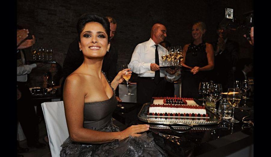 On apporte à Salma un gigantesque gâteau d'anniversaire garni de fruits rouges.
