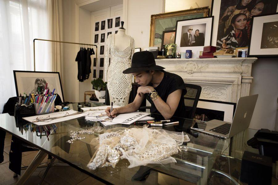 Dans son bureau, rue Pierre-Charron à Paris. Derrière lui, une photo avec Karl Lagerfeld, une autre avec Iman et Naomi. A son poignet, la montre en or offerte par son père.