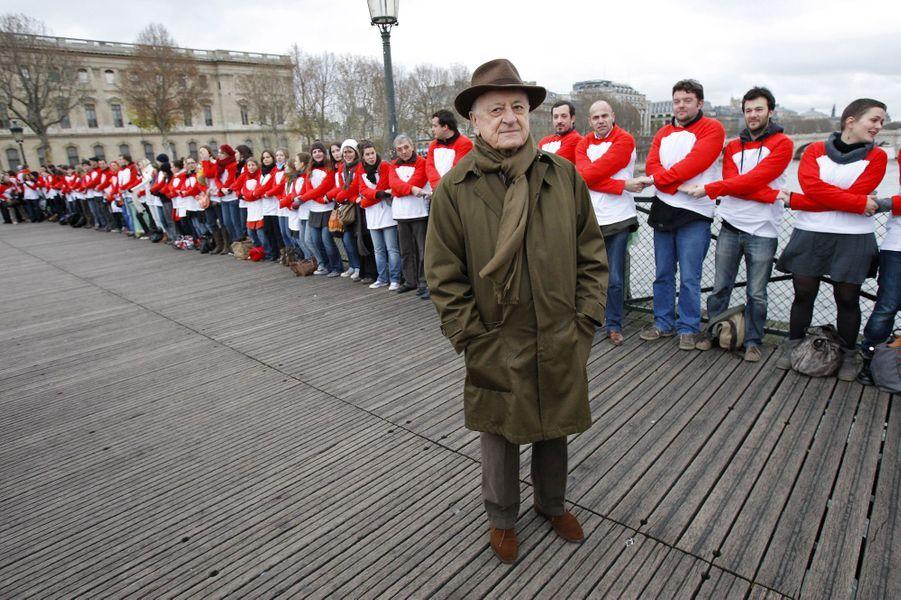 Le 28 novembre 2009, le président du Sidaction Pierre Bergé pose sur le pont des Arts,aux côtés de volontaires venus participer à une chaîne de solidarité.