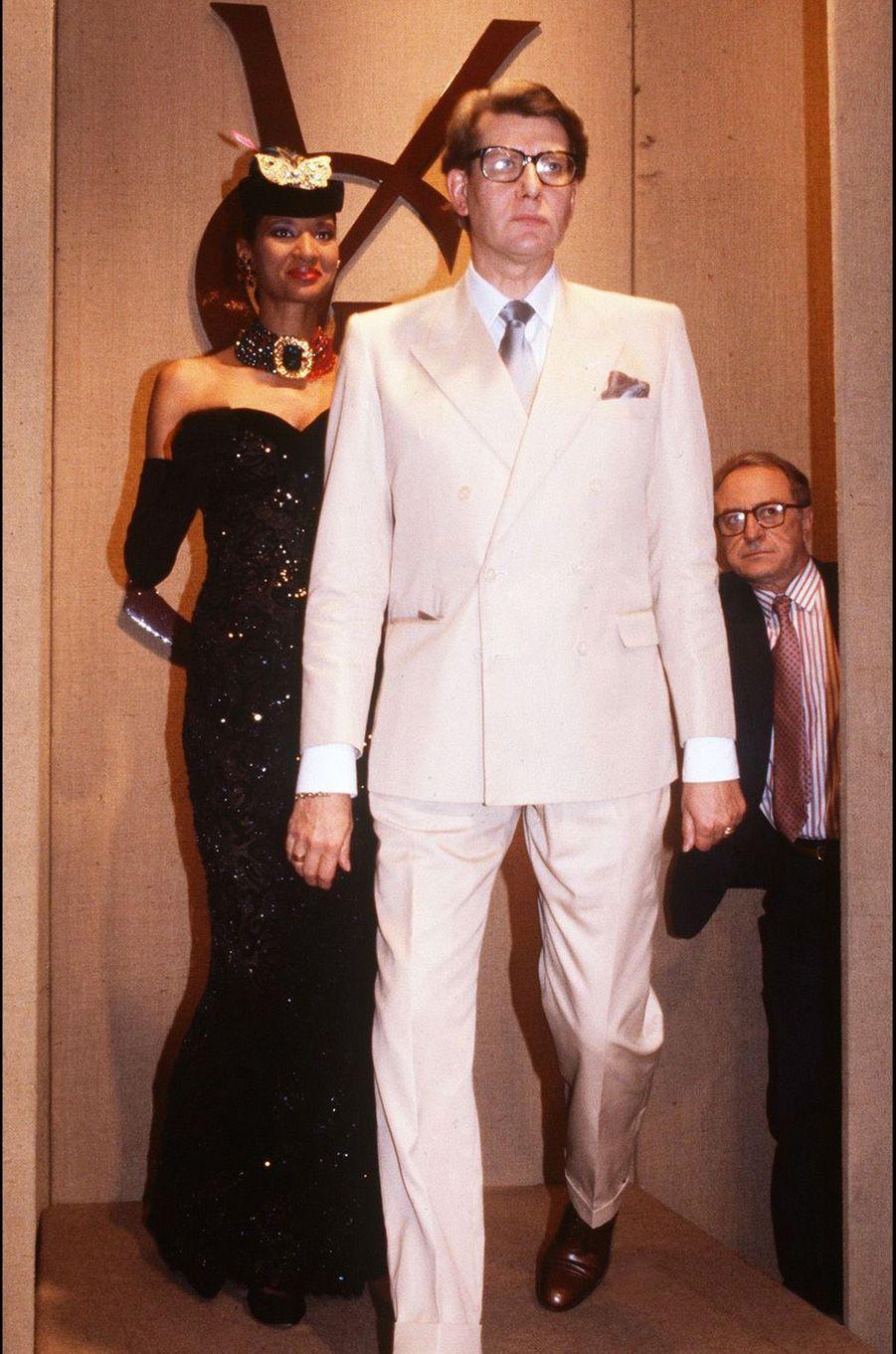Au fond, à droite, Pierre Bergé veille sur Yves Saint Laurent qui fait son entrée pour saluer le public à l'issue du défilé, en juillet 1984, de présentation de sa collection haute-couture automne-hiver 1984-1985.