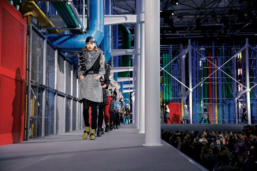 Louis Vuitton recrée Beaubourg au Louvre. En tête de file, veste-cape en laine et robe en tweed rebrodées de sequins, bottines en cuir tressé. Mardi 5 mars.