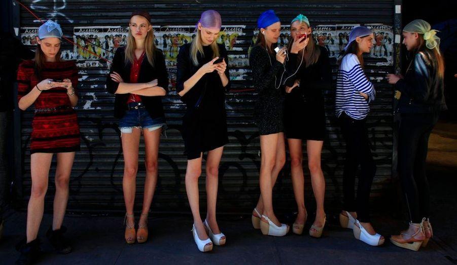 Des mannequins coiffés de foulards se changent les idées à l'extérieur avant de défiler pour la marque Edun à la Fashion Week de New York, heir.
