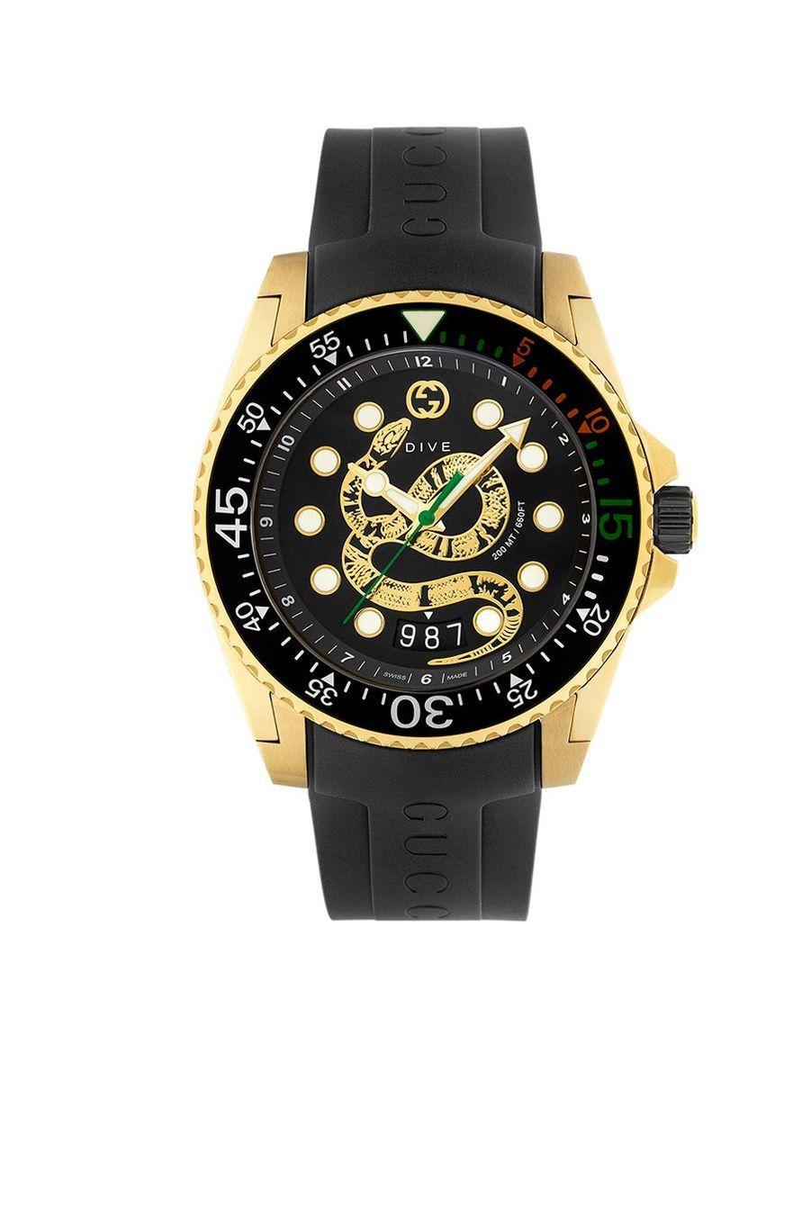 Dive en acier PVD or jaune, 45 mm de diamètre, cadran noir représentant un serpent, mouvement à quartz avec date traînante, bracelet en caoutchouc. 1 350 €. Gucci.