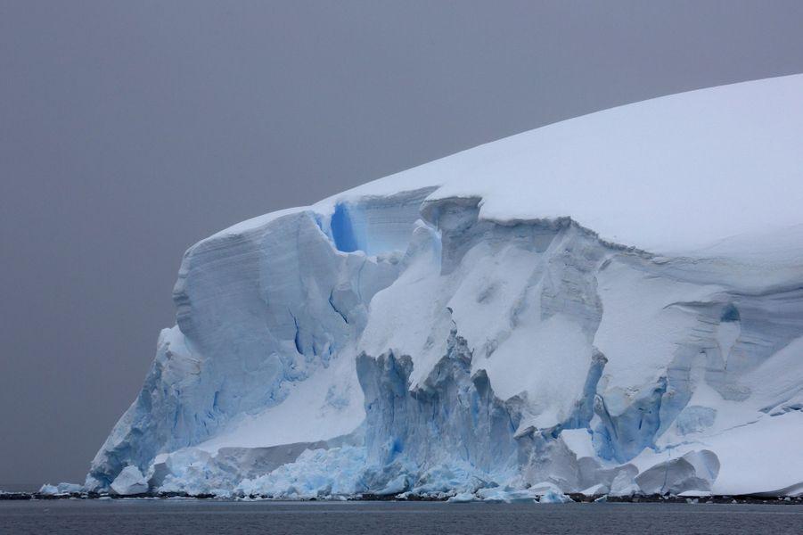 Quand le soleil disparaît derrière des nuages, les glaces rayonnent d'un bleu surnaturel, comme le bord de cet immense glacier (environ 60 mètres d'épaisseur), dans la baie de Wilhelmina, le 23 décembre.
