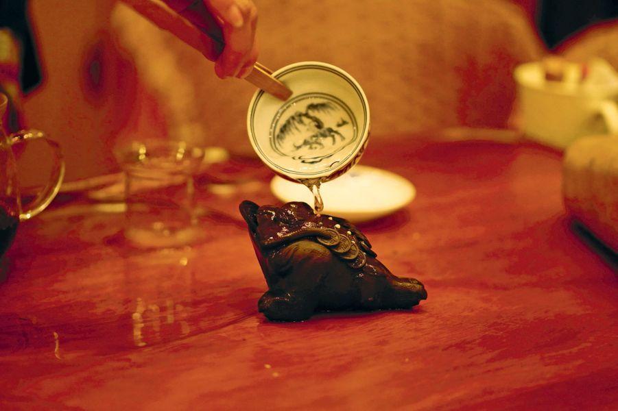 Une grenouille en terre est arrosée de thé afin de porter bonheur.