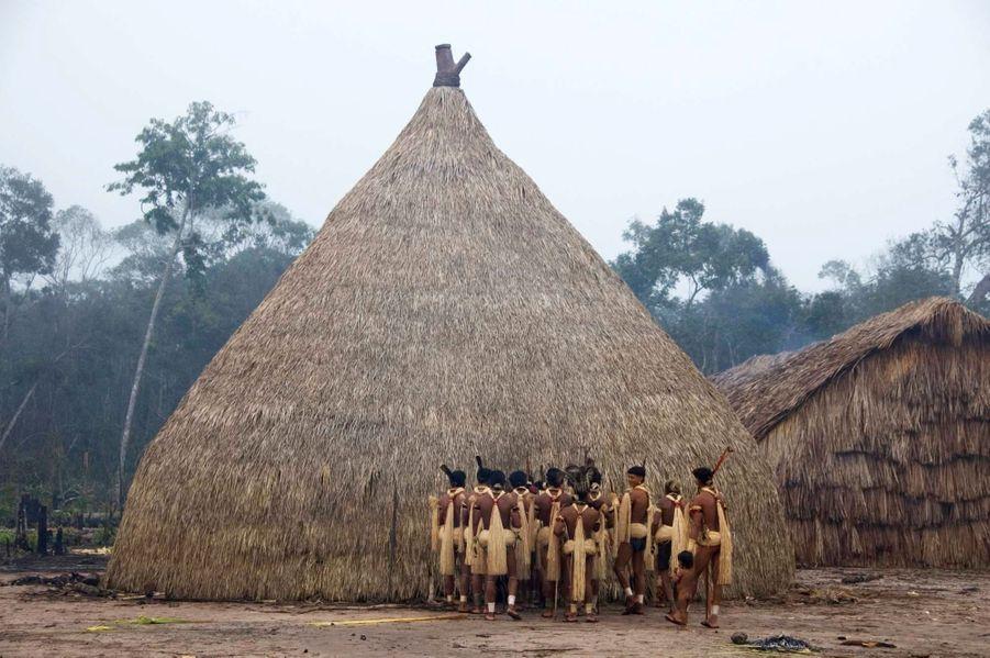 Aux premières lueurs de l'aube, les hommes enanewe nawe de l'Etat du Mato Grosso au Brésil se réunissent devant la maison des flûtes sacrées –haiti. Ils sont récemment revenus de leurs campements dans la forêt pour célébrer la plus importante cérémonie de pêche de l'année, le banquetYãkwa. Les Enawene Nawe sont des pêcheurs aguerris. Pendant la saison sèche, ils capturent les poissons à l'aide d'un poison – timbó – extrait d'une liane grimpante. Des fagots de lianes sont plongés dans l'eau, libérant le poison et asphyxiant les poissons qui remontent à la surface.