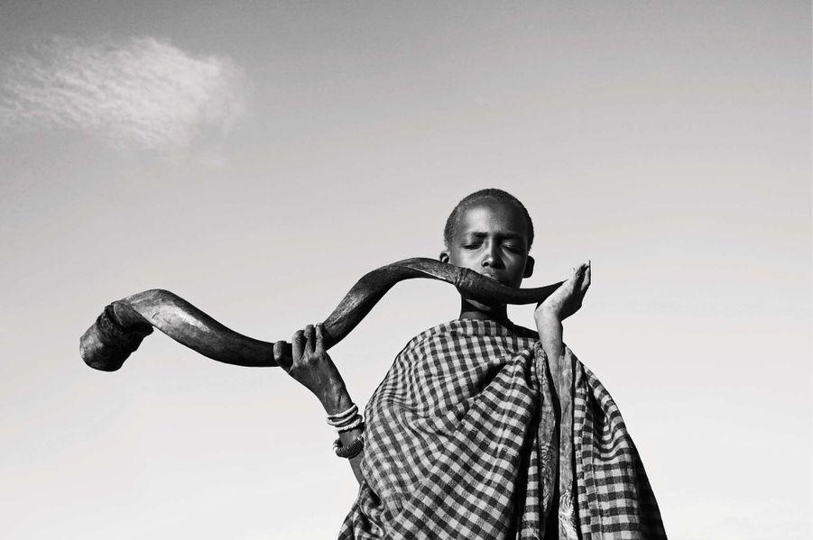 """Les fêtes indigènes rendent également hommage aux cycles de la vie humaine. En Afrique de l'Est, un jeune Maasai souffle dans la corne en spirale d'un Grand kudu pour appeler les moran (adolescents) à la cérémonie """"e unoto"""", qui annonce leur passage à l'âge adulte. La cérémonie accompagnée de chants et de danses dure plusieurs jours."""