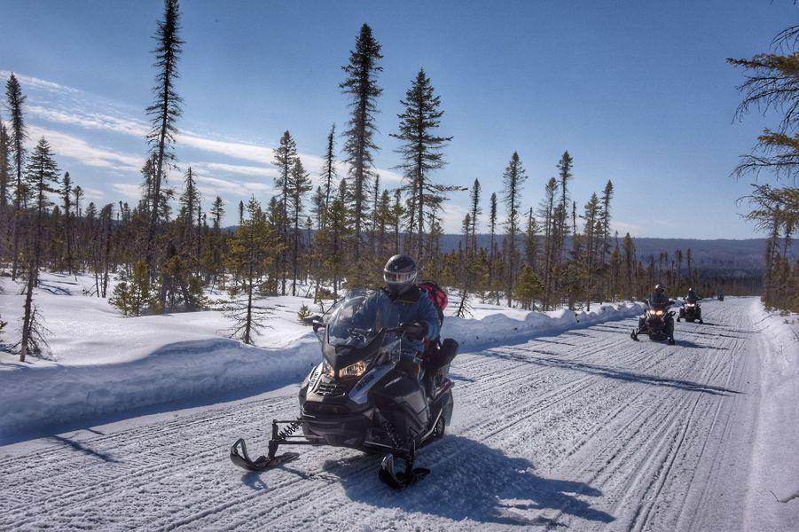 Motoneigistes roulent sur une grande étendue enneigée.