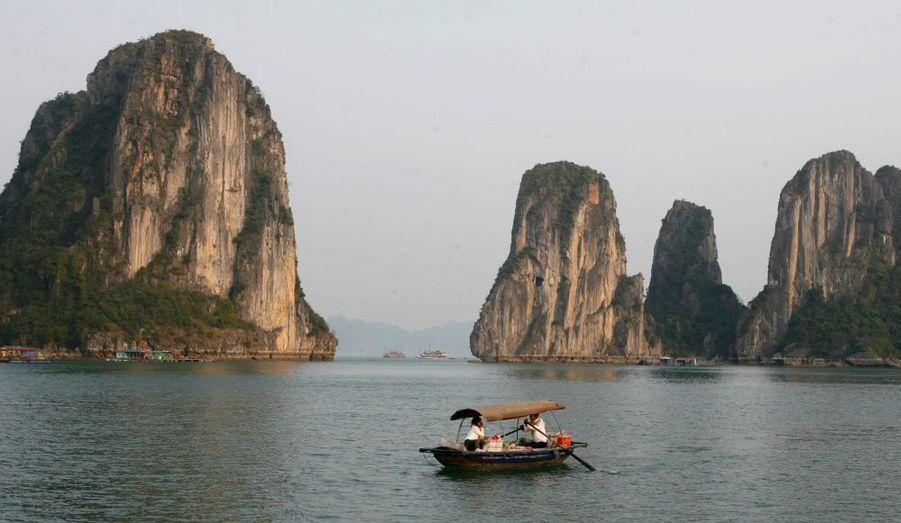 """La baie de Hạ-Long s'étend sur 1 500 km² au nord du Viêt Nam. De nombreuses îles karstiques, paysages façonnés dans la roche, ont fait sa renommée. Hạ-Long signifie """"descente du dragon"""" en vietnamien. La légende raconte que le paysage a été causé par un dragon, être vénéré et bénéfique dans le pays. La créature serait descendu dans la mer pour contrôler les courants marins et dans sa lutte, il aurait entaillé la montagne avec sa queue. Le niveau de l'eau serait alors monté, laissant uniquement les sommets les plus élevés visibles à la surface."""