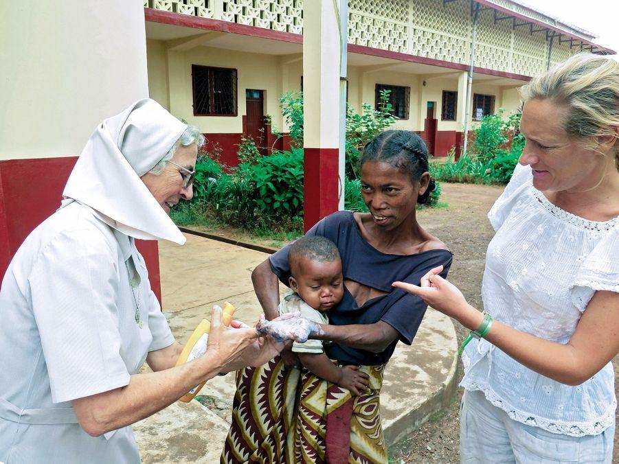 Sœur Teodora soigne les lésions d'une lépreuse. Grâce aux Poussin, l'hôpital de Farafangana aura un nouvel appareil à rayons X.