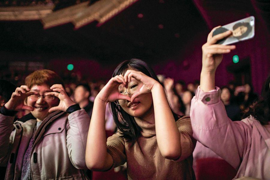 Dans la salle, les fans envoient aux chanteurs des cœurs avec les doigts.