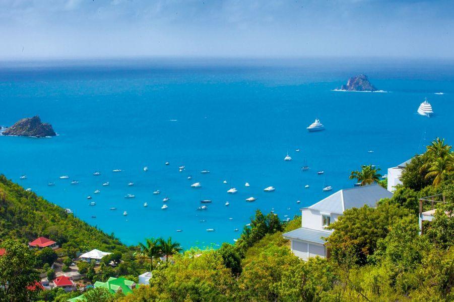 Tout Saint-Barth résumé en une image : une baie bleu azur, des villas aux toits rouges et des yachts de rêve amarrés.