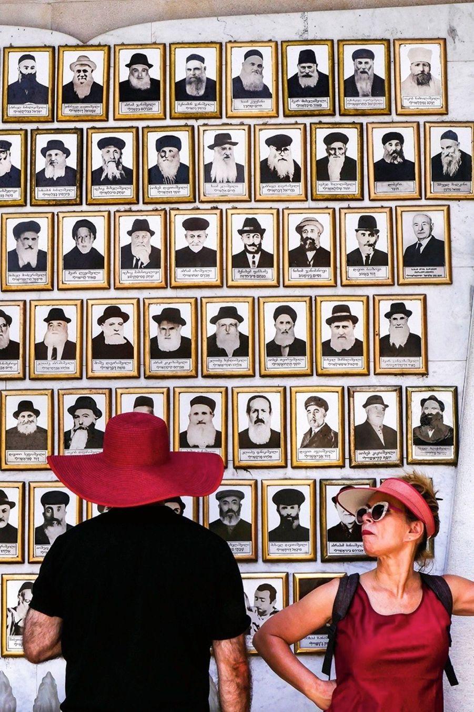 Des visiteurs devant une collection de photos de popes illustres.