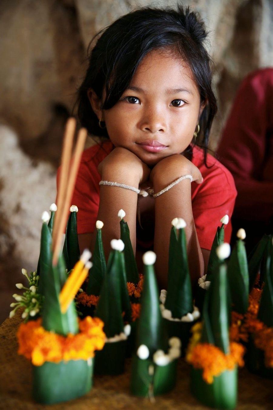 Escale aux grottes de Pak Ou, près de Luang Prabang, ornées de 4 000 icônes de bouddha, dont cette petite fille est (avec sa maman), l'une des gardiennes